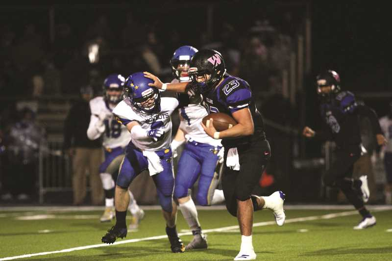 PMG PHOTO: PHIL HAWKINS - Woodburn senior Dyontae Navarrete was a triple-threat for the Bulldogs, rushing for 87 yards, catching three passes for 28 yards and completing six passes for 26 yards in the Bulldogs' 31-6 loss to Crook County on Friday.