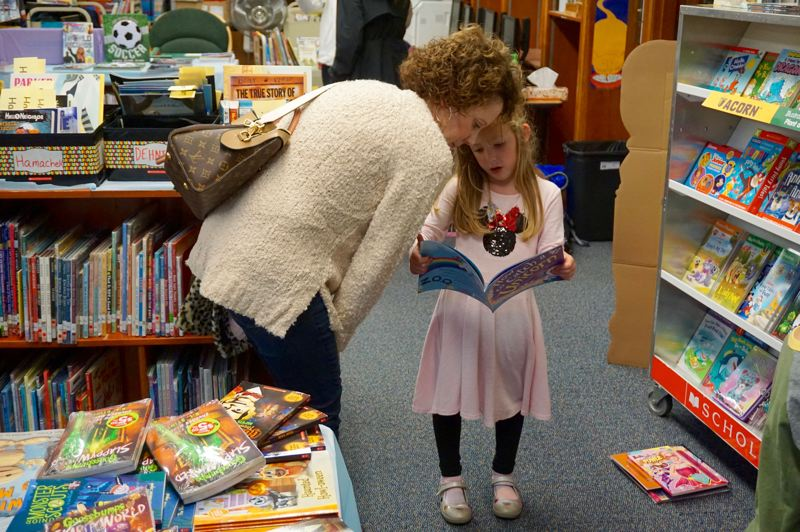 PMG PHOTO: CLAIRE HOLLEY - Kristi Reichlein and her daughter Morgan check out a unicorn book.