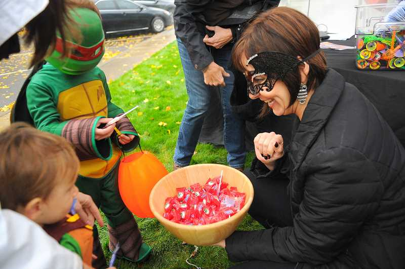 PMG FILE PHOTO - Kids trick-or-treating in the Willamette area get candy from a grown-up.