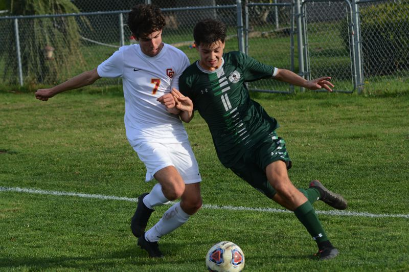 PMG PHOTO: DAVID BALL - Reynolds Rogelio Uribe Rodriguez rushes onto a ball in the corner against Central Catholics Sam Duncan-Doroff.