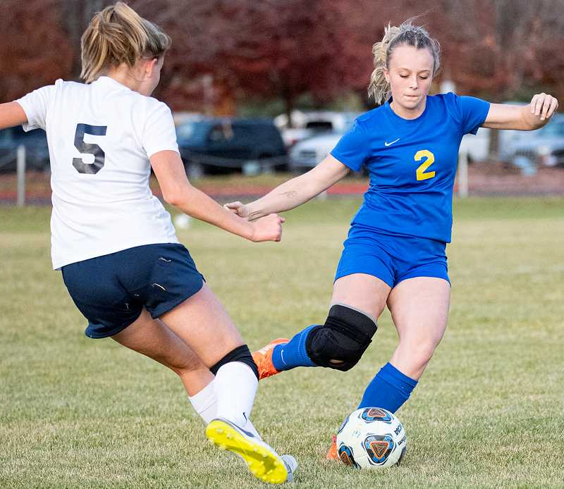 LON AUSTIN/CENTRAL OREGONIAN - Teagan Freeman plays a ball away from Hood River Valley forward True Becker during Crook County's 7-0 loss to the Eagles on Tuesday. The Cowgirls play their final home match of the season next Tuesday against the league-leading Ridgeview Ravens.