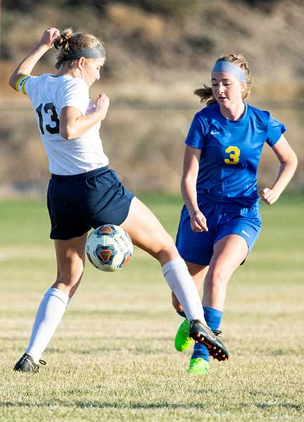 LON AUSTIN/CENTRAL OREGONIAN - Grace Slawter plays a ball past a Hood River Valley defender during the Cowgirls' 7-0 loss to the Eagles on Tuesday. The Cowgirls play their last home match on Tuesday when they host Ridgeview.