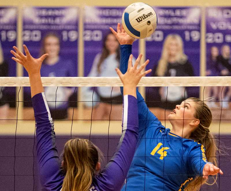 LON AUSTIN/CENTRAL OREGONIAN - Kenna Woodward tips the ball for a kill against a Ridgeview blocker. Woodward led the Cowgirls in kills with 13 in the match.