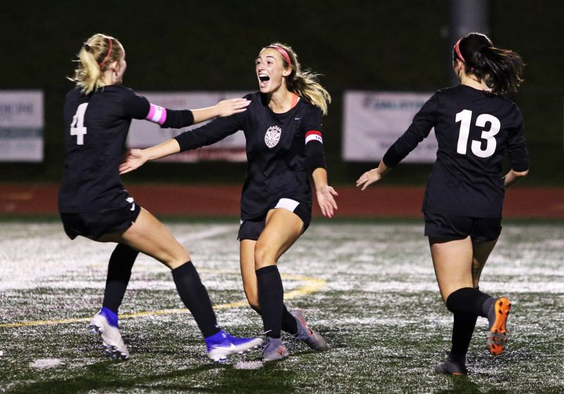 PMG PHOTO: DAN BROOD - Tualatin High School senior Abby Borg (center) celebrates with senior Aden Lynch (4) and junior Alyvia Embree after scoring in the 3-0 victory over Lakeridge.