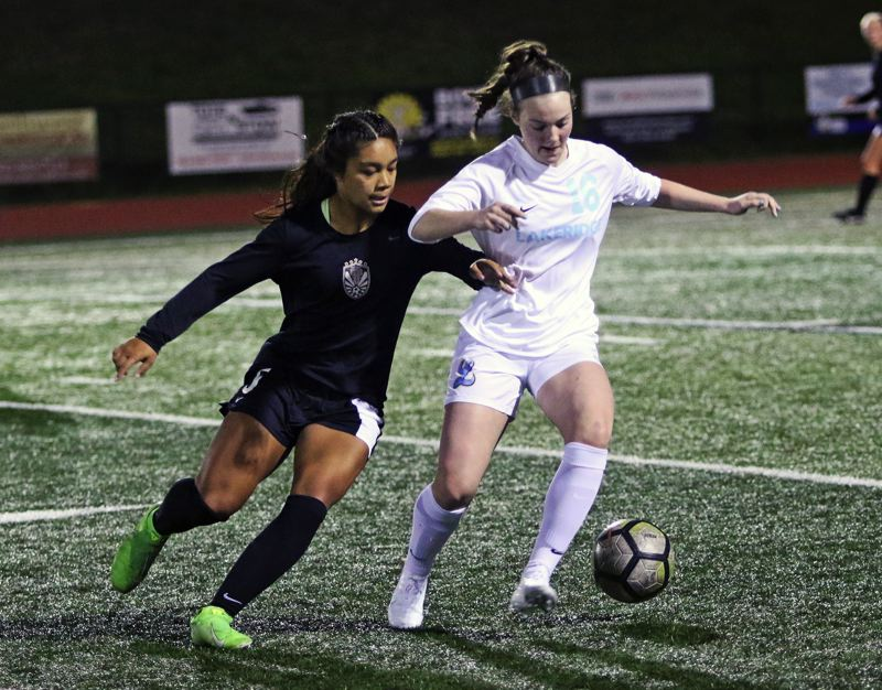 PMG PHOTO: DAN BROOD - Tualatin High School junior Cally Togiai battles Lakeridge junior Jenna Barouh for the ball during Thursday's match. Togiai scored a pair of goals in the Wolves' 3-0 victory.