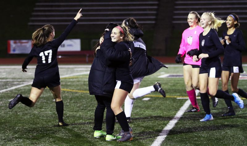 PMG PHOTO: DAN BROOD - Members of the Tualatin High School girls soccer team, including, from left, Brook Burke, Cally Togiai, Darci Chamberlin, Sarah Hall, Payton Wesson and Maya Loudd start celebrating following the end of the team's 3-0 win over Lakeridge.