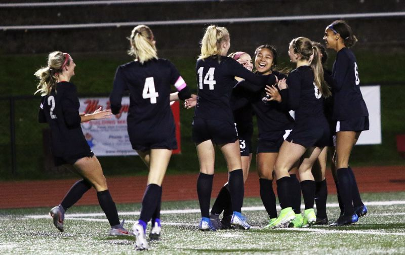 PMG PHOTO: DAN BROOD - Members of the Tualatin High School girls soccer team celebrate with Cally Togiai after she scored the first of her two goals in the Wolves' 3-0 win over Lakeridge.