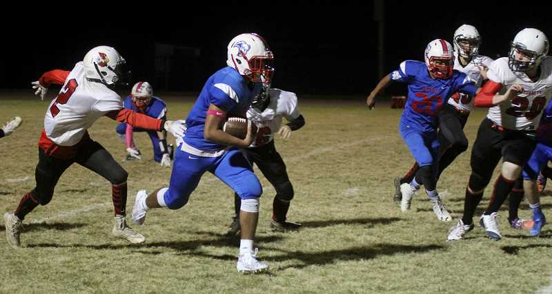 STEELE HAUGEN - Donnie Bagley carries the ball for Madras during the White Buffalos' 22-0 win over Corbett Oct. 25.