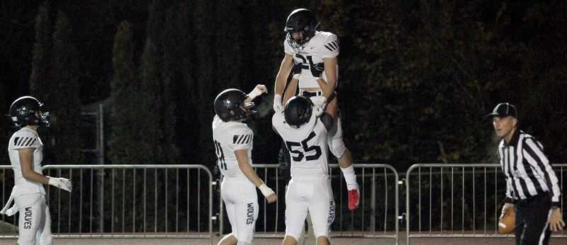 PMG PHOTO: MILES VANCE - Tualatin senior running back Kainoa Sayre gets lifted into the air by senior teammate Cody Van Meter after Sayre scored the first of his three touchdowns in the Timberwolves' 34-8 win over Lake Oswego at Lake Oswego High School on Friday, Oct. 25.