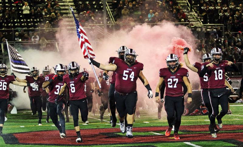 PMG PHOTO: DAN BROOD - The Sherwood High School football team takes the field prior to Friday's Pacific Conference contest against Liberty.