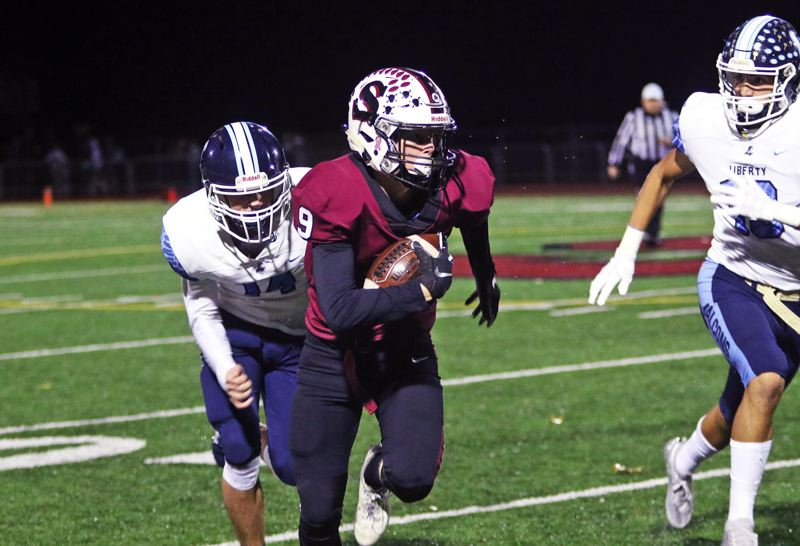 PMG PHOTO: DAN BROOD - Sherwood High School junior receiver Jackson Hughes picks up extra yardage during the Bowmen's 56-7 Pacific Conference win over Liberty on Friday.