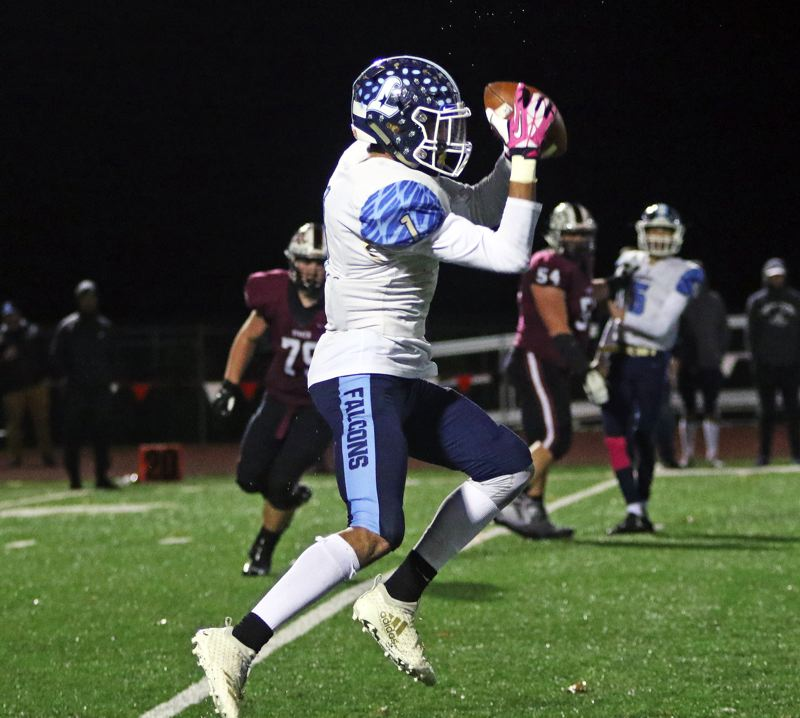 PMG PHOTO: DAN BROOD - Liberty High School senior receiver Marquis Brown goes up to make a catch during the Falcons' loss at Sherwood on Friday.