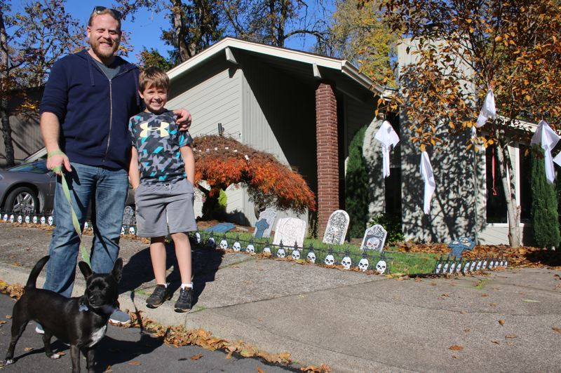 Bob and Lachlan Higgins stand in front of their home on Wilderness Drive.