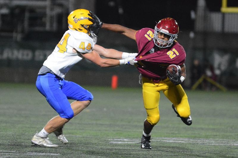 PMG PHOTO: DAVID BALL - Central Catholic's Miles Jackson (right) tries to get away from Barlow's Nick Colloins during the Rams' 53-14 win on Friday, Oct. 25.