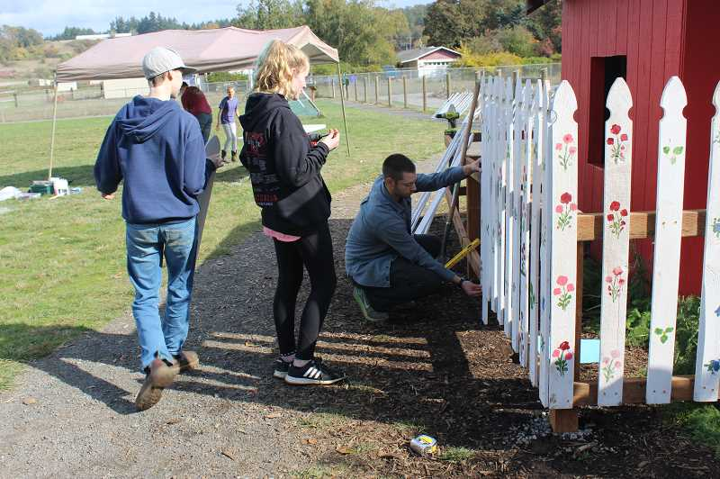 PMG PHOTO: KRISTEN WOHLERS - Adults and older students install the fence posts around a playhouse on Molalla River Academy's grounds Oct. 18.