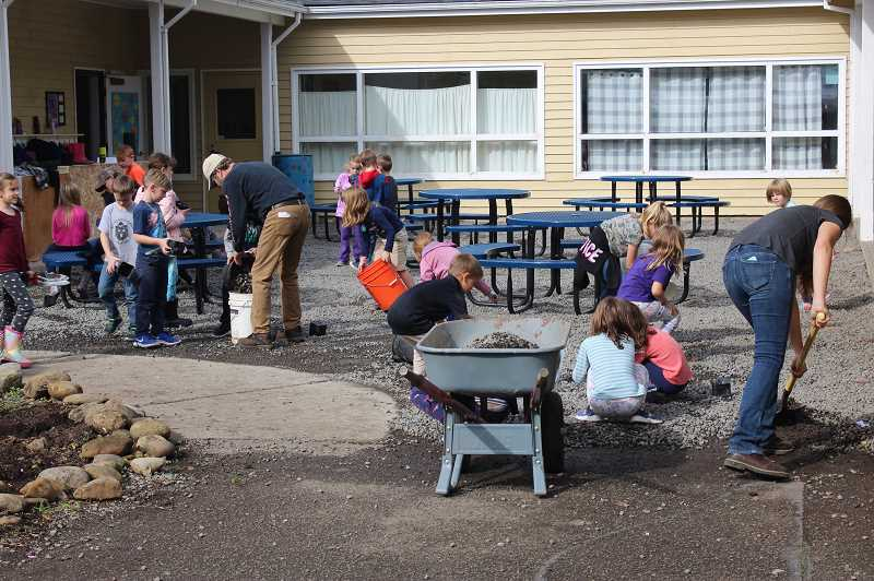 PMG PHOTO: KRISTEN WOHLERS - Students at MRA work to remove gravel from a common area to prepare for a stone patio to be placed.