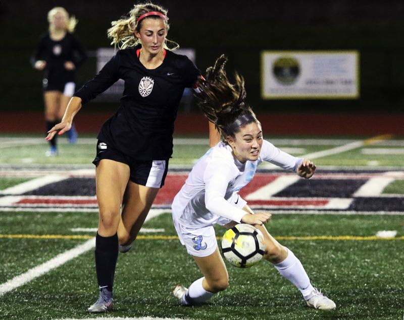 PMG PHOTO: DAN BROOD - Lakeridge High School junior Bella Yannello (right) is knocked down as she battles Tualatin senior Abby Borg for the ball during Tualatin's 3-0 home win on Thursday, Oct. 24.