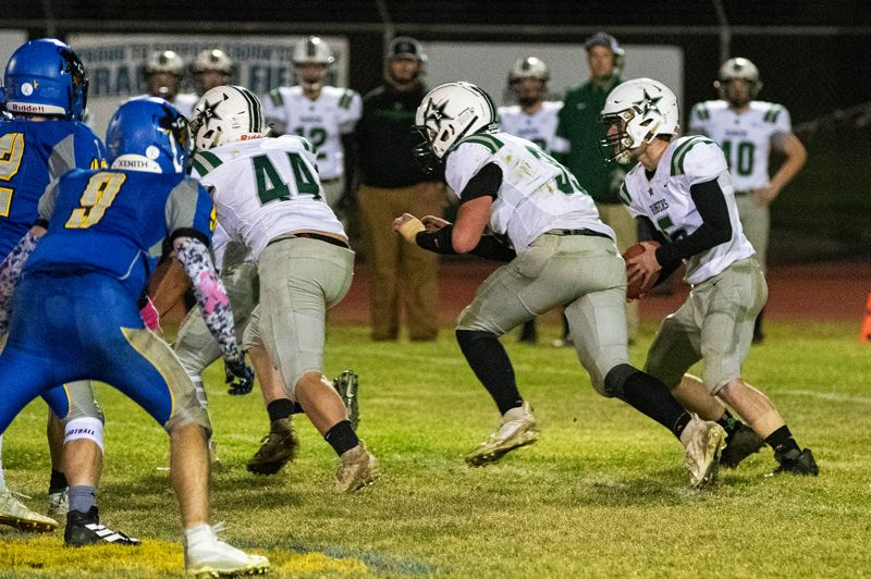 PMG PHOTO: LON AUSTIN - Estacada QB Isaiah Schaffer (5) follows blockers around the right side during Fridays 38-13 road win at Crook County.