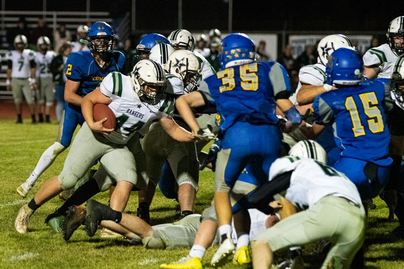 PMG PHOTO: LON AUSTIN - Estacada running back Waylon Reidel looks for a path around the corner.