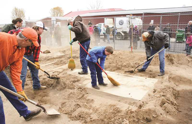 CENTRAL OREGONIAN - Volunteers hustle to dig out the contents of the pit barbecue, one of the most popular attractions of Lord's Acre Day, an event that began more than 70 years ago as a fundraiser for Powell Butte Christian Church.