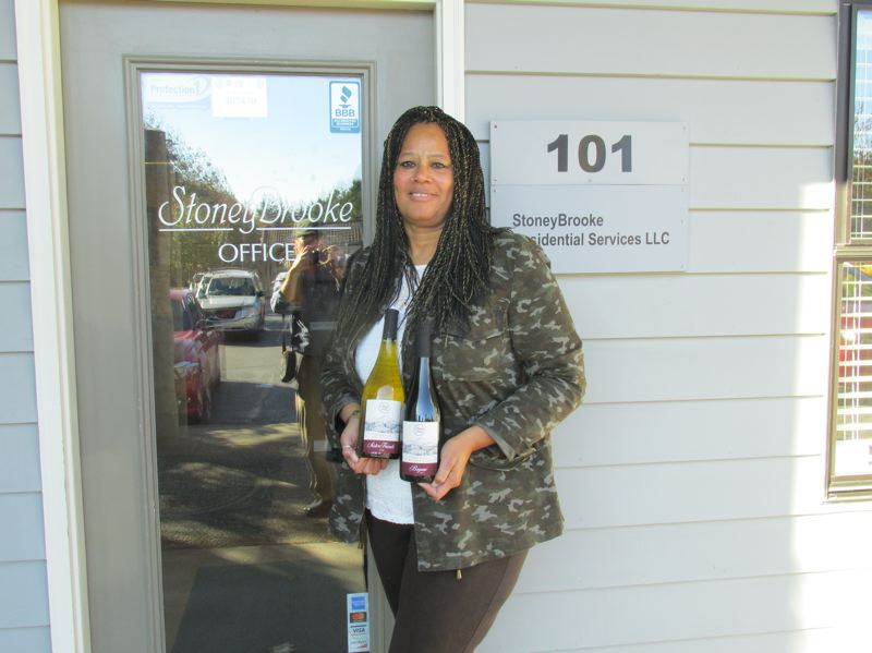 PMG PHOTO: SHANNON O. WELLS - Donna Stoney, co-founder of StoneyBrooke Residential Services in Gresham and Oregons first black female winemaker, shows off her Bayani Pinot red and SisterFriends Chardonnay outside her office at StoneyBrooke.