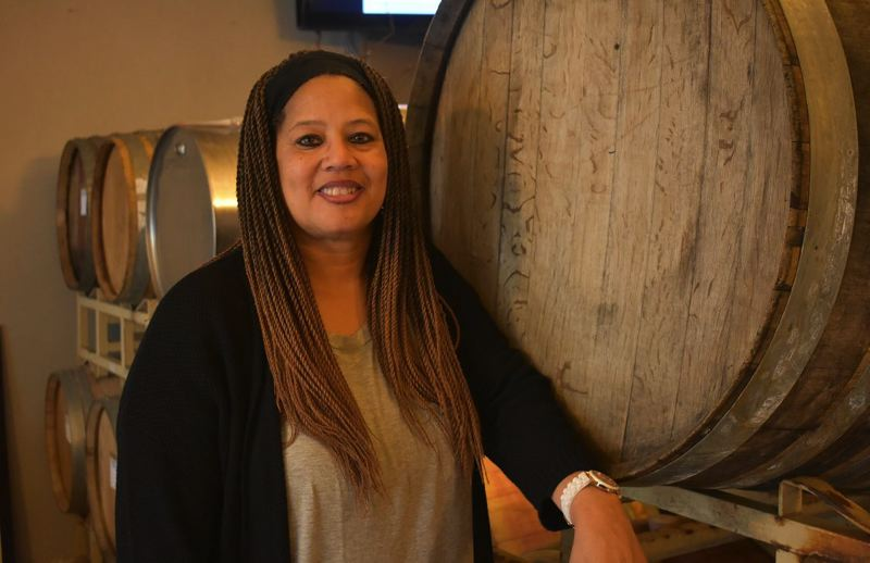 PMG PHOTO: SHANNON O. WELLS - Donna Stoney poses by a wine barrel at Abbey Creek Vineyards in North Plains, where she learned the finer points of winemaking from owner Bertony Faustin, Oregons first black owner of a winery.
