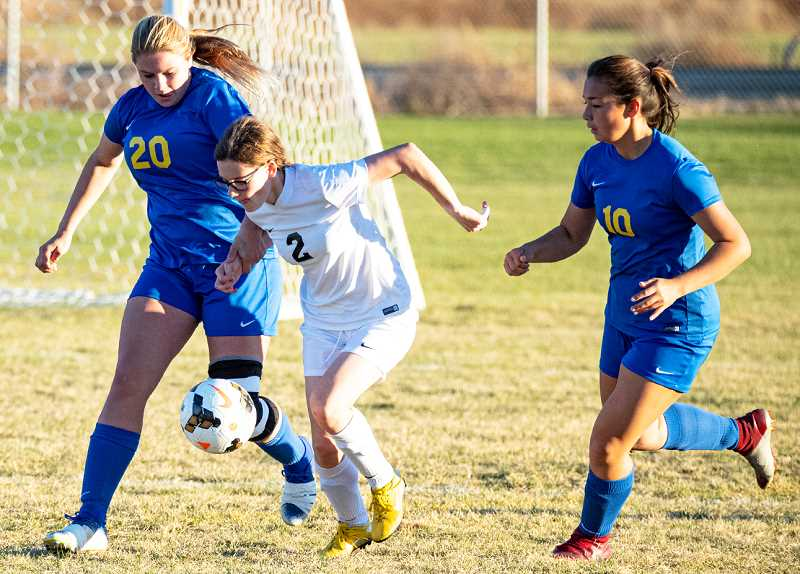 LON AUSTIN/CENTRAL OREGONIAN - Emma Bales, 20, and Jaidyn Hammack, 10, work to take the ball away from Pendleton forward Reilly Lovercheck during the Cowgirls' match with the Buckaroos last Thursday in Prineville.