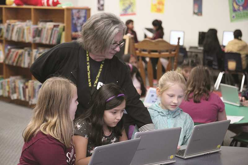 PMG PHOTO: PHIL HAWKINS - Gervais librarian Gina Deffenbaugh assists fourth-grade students Addison Rice, Itzuri Torres Ramirez and Addellaide Gerasimenko during the 45-minute session on Oct. 25.