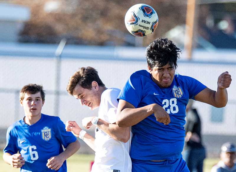 LON AUSTIN/CENTRAL OREGONIAN - Abel Nunez, number 28, heads a ball away from a Pendleton player as Cowboy defender Hayden Shaw looks on. The Cowboys and Buckaroos were tied midway through the second half before Pendleton went on a late surge to win 5-2.