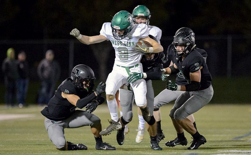 COURTESY PHOTO: CHRISTOPHER GERMANO - West Linn wide receiver Clay Masters tries to escape the Tigard defense during his team's 42-21 loss at Tigard High School on Friday, Oct. 25.
