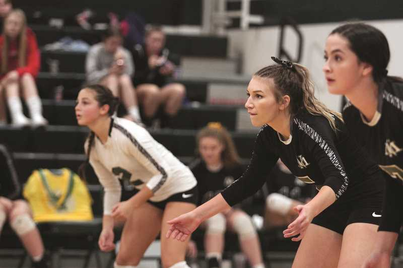 PMG PHOTO: PHIL HAWKINS - From left, backline defenders Megan Netter, Alana Walls and Lily Piercy prepare to receive a serve from Corbett in the fifth set of the Huskies 3-2 loss to the Cardinals on Wednesday, Oct. 23.
