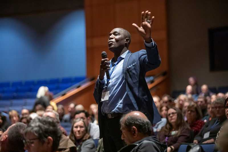 PMG PHOTOS - Lake Oswego resident Massene Mboup asks a question of Marvin Lynn during the Multi-City Equity Summit.