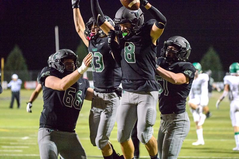 COURTESY PHOTO: CHRISTOPHER GERMANO - Tigard High School senior Josh Burns (8) celebrates with teammates (from left) Bryce Goetz, Mathew Otness and Edward Beglaryan after scoring one of his four touchdowns in the Tigers' 42-21 win over West Linn.
