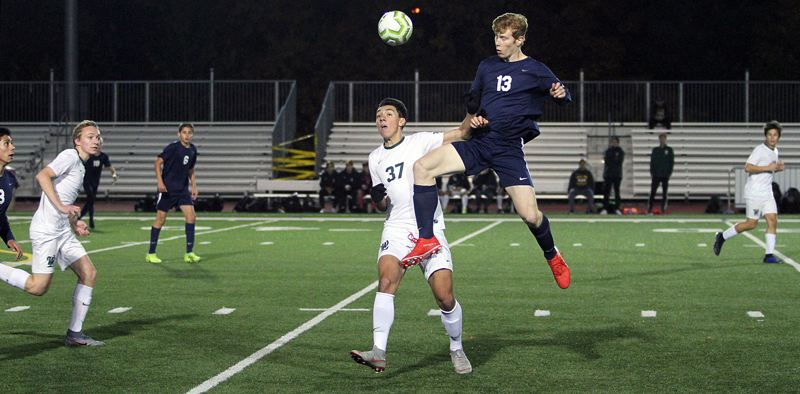 PMG PHOTO: MILES VANCE - Lake Oswego junior defender Jack Woolf leaps over West Linn's Jacob Babalai for a header during the Lakers' 3-2 loss to the Lions at Lake Oswego High School on Thursday, Oct. 24.