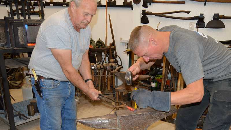PMG PHOTO: CINDY FAMA - After sufficient heating, Kenny Carroll (left) and Shannon Reed hammer the metal.