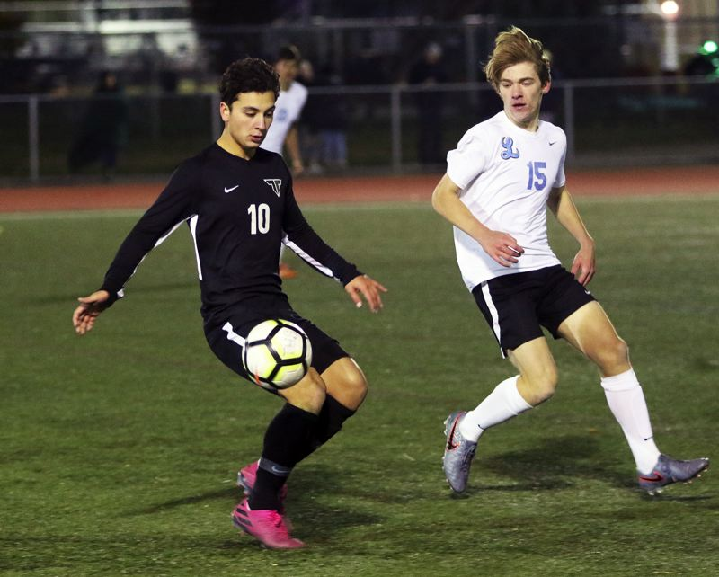 PMG PHOTO: DAN BROOD - Tigard High School senior Marco Millan (10) goes for the ball during the Tigers' 7-0 win over Lakeridge in Tuesday's Three Rivers League contest.