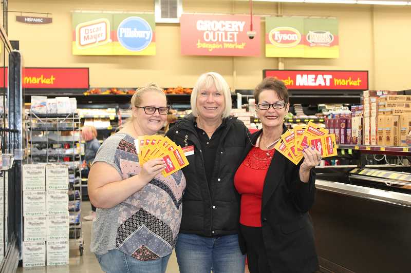 DESIREE BERGSTROM/MADRAS PIONEER - From left to right, Caren Smith, Kids Club operations manager, Rhonda Bourgo, Grocery Outlet owner, and Pat Abernathy, director of the Jefferson County Winter Shelter hold gift cards. Kids Club and the shelter were the recipients of funds from the store's annual Independence from Hunger fundraiser that happens every July.