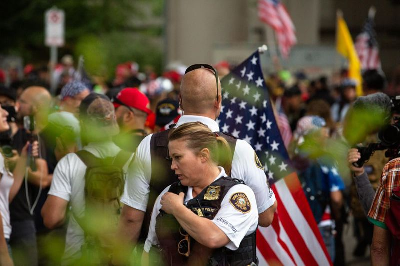 BRADLEY W. PARKS/OPB - Liaison officers with the Portland Police Bureau monitor a white supremacist rally under the Hawthorne Bridge on Aug. 17, 2019. The rally carried the potential for violence and attracted hundreds of antifascist counter-protesters.