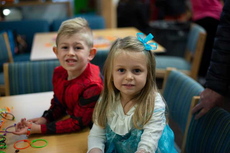 PMG PHOTO: ANNA DEL SAVIO - Siblings who attended Harvest Happenings with their grandparents pause while making bracelets.