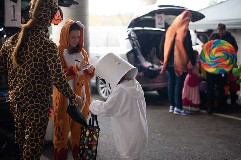 PMG PHOTO: ANNA DEL SAVIO - Volunteers decorate car trunks and hand out candy to students at Stafford Primary School.