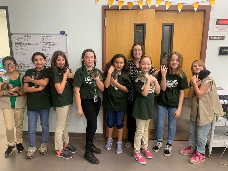 PHOTO COURTESY OF NICHOLE HETLAND - Woodburns  Girl Scout Troop No. 13019 visits Woodburn Pet Hospital, left to right, Sophia Mora, Mercedes Garza, Haylee Rose, Olivia Clark, Ariela Zazueta, Dr. Beth Nguyen, Rhiannon Chiniewicz, Aubrie Hetland, Lindsay Ellis.