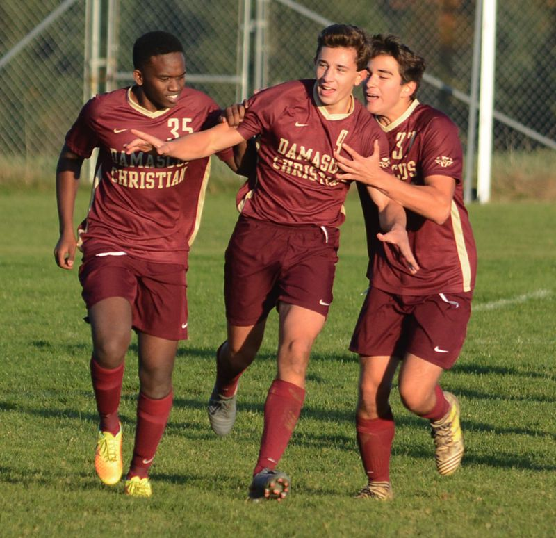 PMG PHOTO: DAVID BALL - Damascus Christians Nate Bogdan (cneter) celebrates with teammates after netting the tying goal midway through the second half.