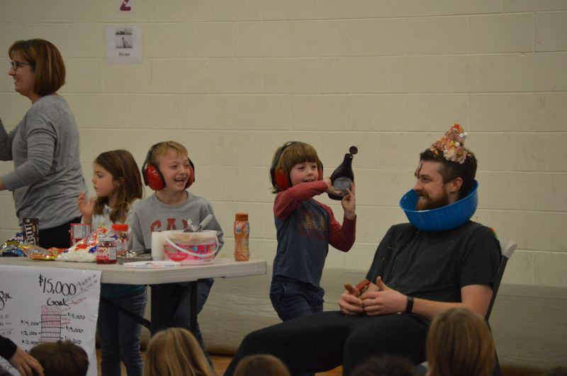 PMG PHOTOS: NICOLE THILL-PACHECO - Students and staff helped scoop ice cream and dump various candy toppings and syrups onto Sheas head during an all-school assembly Monday, Oct. 28.