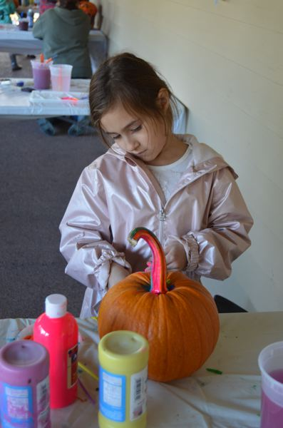 PMG PHOTO: NICOLE THILL-PACHECO - Seven-year-old Alexis Menendez carefully swipes a paintbrush loaded with neon pink paint onto her pumpkin. In addition to coloring the shell, Menedez also decorated the stem of her gourd at the library event.