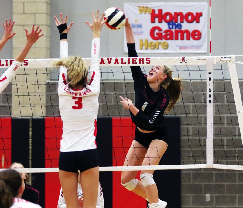 PMG PHOTO: DAN BROOD - Sherwood High School senior Alli Douglass (right) smacks the ball over the net during the Lady Bowmen's state playoff win at Clackamas on Oct. 30