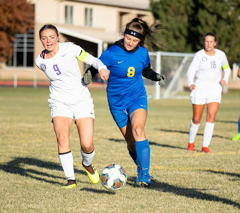 LON AUSTIN/CENTRAL OREGONIAN - Mariah Cannon, 8, fights with Ridgeview's Aria Mascal for the ball during the two teams' Intermountain Conference match Tuesday in Prineville. It was senior night for the Cowgirls, who lost 7-0.