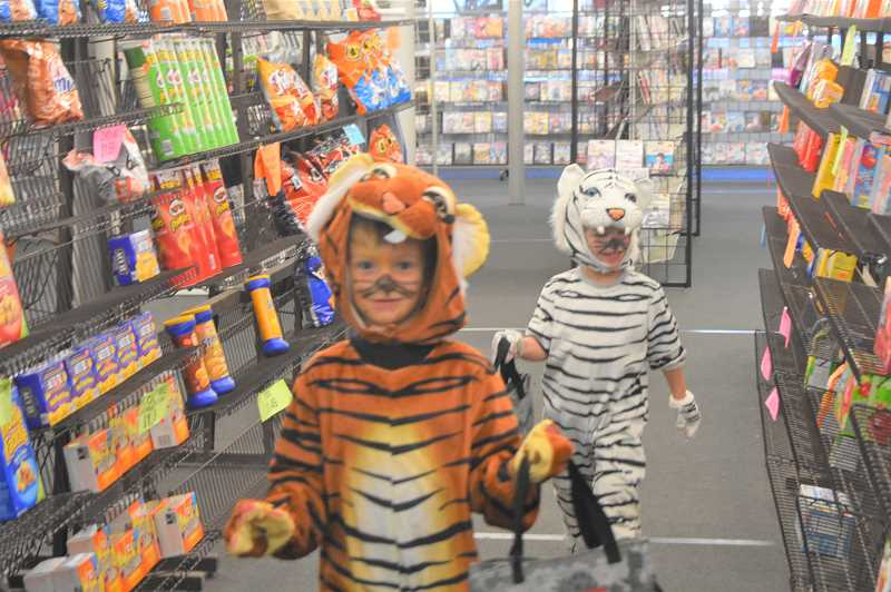 PMG PHOTO: EMILY LINDSTRAND - Young Creepy Crawl participants prepare to collect candy at Just In Video.
