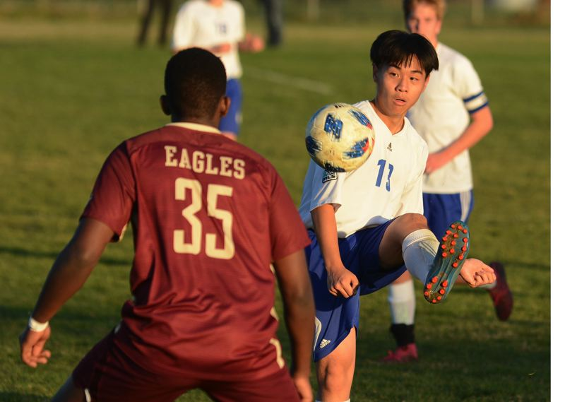 PMG PHOTO: DAVID BALL - North Clackamas Christians John Wang plays a ball deep in the attacking zone during the Saints 3-2 playoff win at Damascus Christian on Monday.