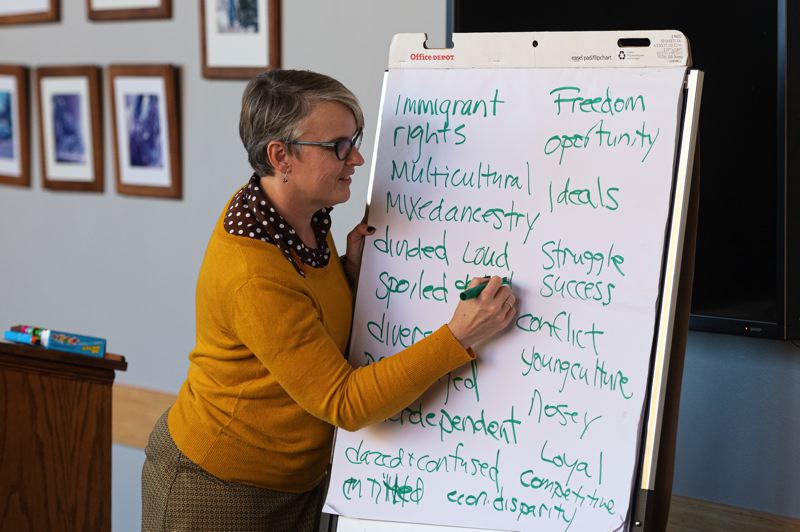 PMG PHOTO: CHRIS OERTELL - Ellen Knutson, an associate professor at the University of Illinois, writes brainstormed words on what being an American means to participants during a community discussion at Pacific University.