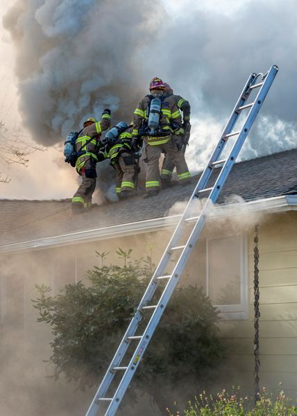 COURTESY PHOTO: TUALATIN VALLEY FIRE & RESCUE - Firefighters work to ventilate the roof of a house on fire in Tualatin Friday morning, Nov. 1.